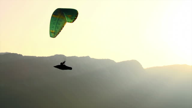 HD: Backlit Silhouette Of A Paraglider