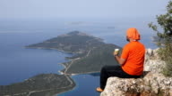 Backpacker is watching the mediterranean sea while drinking coffee