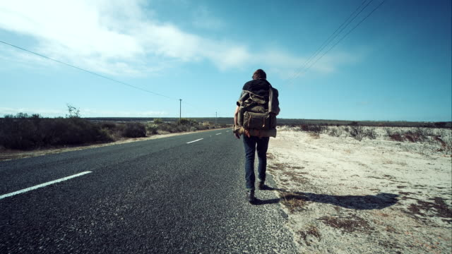 Backpacker walking along road