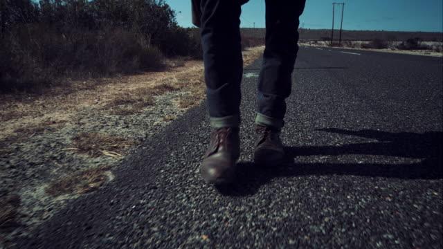 Backpacker walking along road