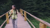 Backpacker woman crossing wooden bridge