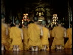 Backs of Buddhist monks kneeling and praying small golden Buddha statue Thailand