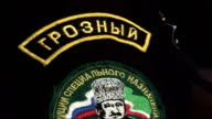 Badge sewn on arm of member of Kadyrov's security forces High angle shot of crowd with uniformed members of security forces in the background Back...