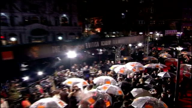 London Leicester Square Umbrellas held up by people on red carpet Long shot of BAFTA Nominated actor George Clooney as interviewed on the red carpet...