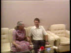 IRAQ Bagdad Abu Ghraib Prison TX MS Shirley Ian sitting down together on sofa CMS Hands holding CMS Both smiling