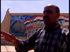 Baghdad EXT BV Colonel Rashid Abu AlIzz along with Hilsum in front of large mural of Saddam Hussein TRACK shooting pistol at mural CBV Rashid firing...
