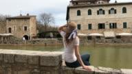 Bagno Vignoni, Siena, Orcia Valley, Tuscany. Girl admiring the view in Bagno Vignoni