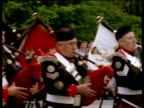 Bagpipers march past camera during parade spectators in background