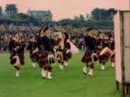 MONTAGE Bagpipers wearing kilts and marching in formation on a field / Scotland, United Kingdom