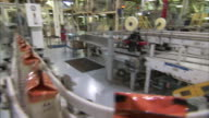 Bags of packaged coffee move along a conveyor belt in a factory.