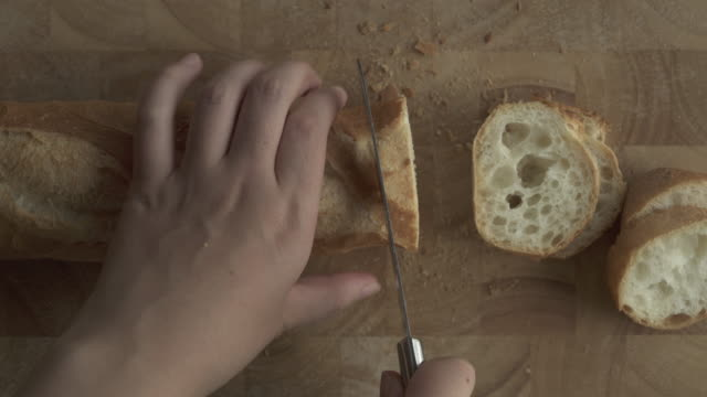 Baguette cutting on wooden cutting board