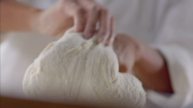Baker kneads and shapes dough with her hands