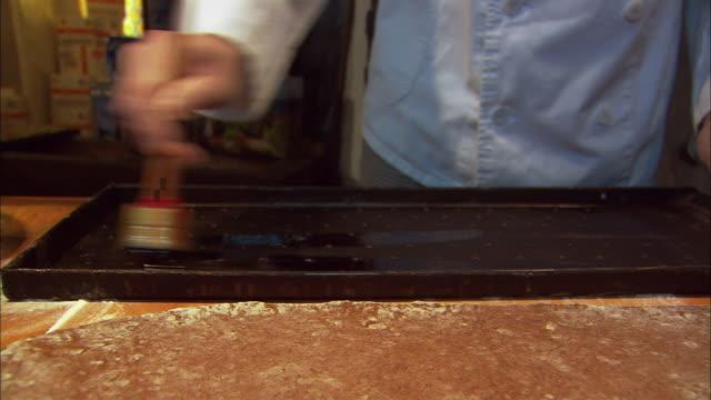 MS Baker making traditional Gingerbread (Lebkuchen), spreading honey on tray / Nuremberg, Bavaria, Germany