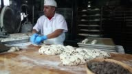 A baker rolls dough as he makes bread at Boudin Bakery on March 11 2015 in San Francisco California