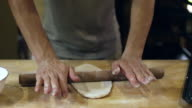 A baker uses a rolling pin to roll out bread dough