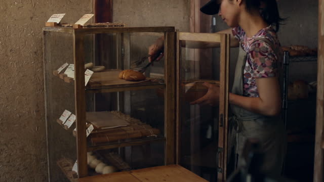 A bakery owner puts various bread on display for sale