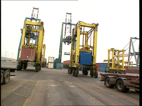 Record Debt LIB ENGLAND Kent Tilbury Containers stacked in container port TRACK LR Mobile cranes carrying containers to be loaded onto lorries along