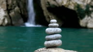 Balanced stones on waterfall background