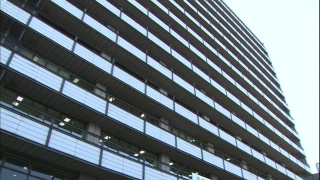 Balconies and windows line a facade of the Kumamoto City Hall.