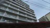 Balconies line a facade on a Toyama apartment complex building.