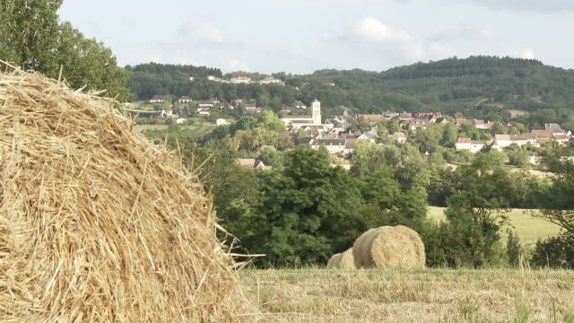 MS Bale of straw infront of small village / Nevers, Burgundy, France