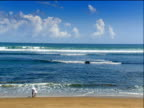 Balinese man in white robes on golden sandy shore bends and touches water then looks out towards breaking waves Bali