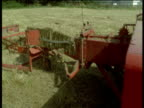 Baling machine moves past camera, hay bales come out of rear of machine, Devon
