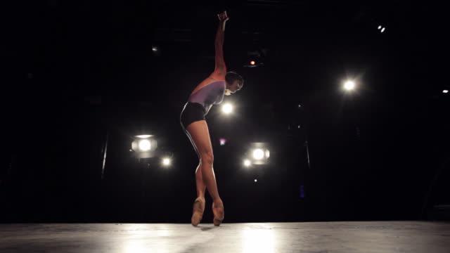 WS Ballerina on stage dancing modern ballet under stage lights / New York City, New York, USA