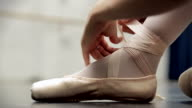 Ballerina ties up her pointe shoes - close up