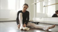 Ballerina tying the ribbon on her ballet shoes.
