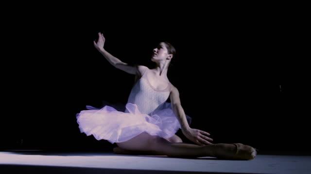 MS Ballerina wearing tutu under spotlight performing death / New York City, New York, USA