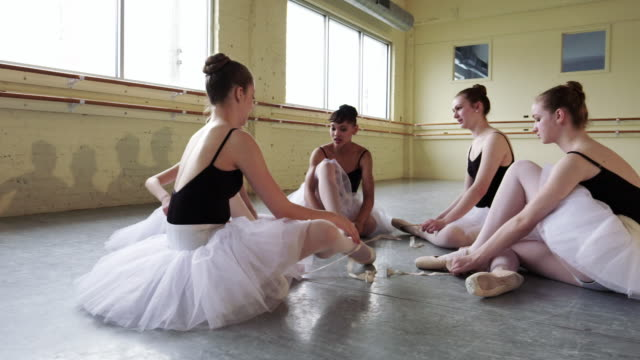 Ballerinas sitting on floor removing pointe shoes