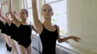 Ballerinas standing at barre with arms raised