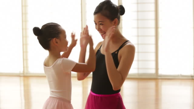 MS Ballet teacher congratulating young student.