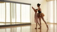 WS Ballet teacher teaching young ballerina to dance in front of a mirror.