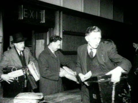 Ballot boxes are delivered to a counting station and the ballots poured onto a table to be counted during the 1951 General Election 25 October 1951