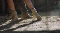 CU SLO MO. Ballroom dancers stomp, twirl, drag, and pose with their feet on dusty barn floor.