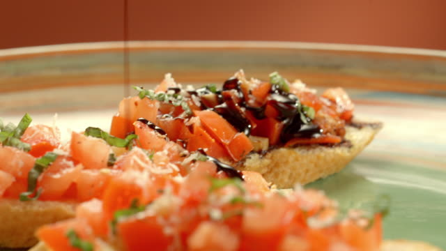 CU R/F balsamic poured over bruschetta, a mixture of chopped tomatoes, basil and garlic on slices of toasted baguette