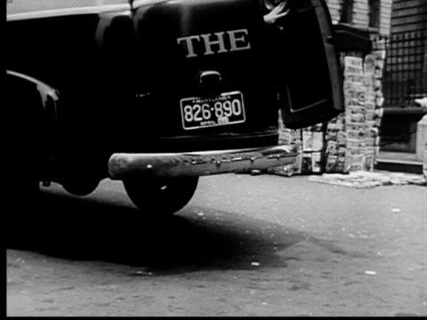1953 MS Baltimore Sun newspaper truck speeding to halt/ Truck doors opening as throws papers on sidewalk/ TU Man picking up bundle of papers and carrying it to news stand/ Baltimore, Maryland