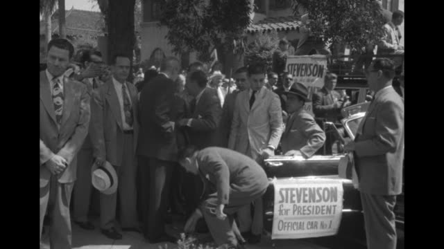 Bandwagon comes to stop and crowd applauds as Democratic Party presidential candidate Adlai Stevenson appears / he speaks on porch of large home...