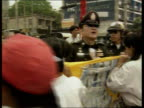 Bangkok CMS Boy demo using megaphone to speak to crowd sitting on ground SOT MS More ditto GV Grass area full of demos with riot police lined up in...
