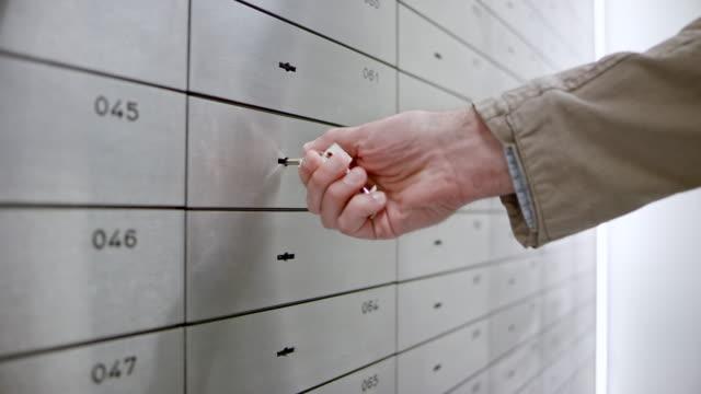 Vault-PAN Bankkaufmann und männlicher Kunde Entriegelung den Safe in der bank