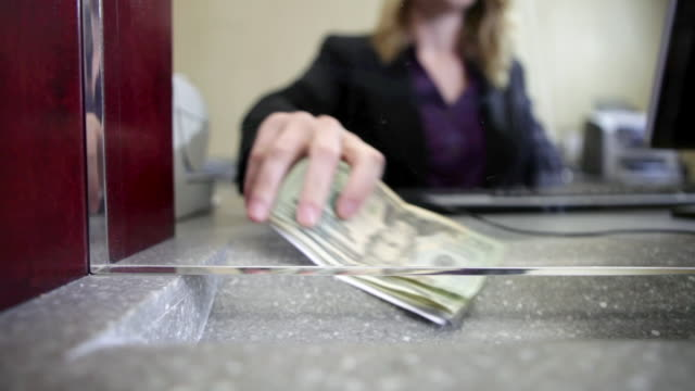 Bank teller counting money in bank