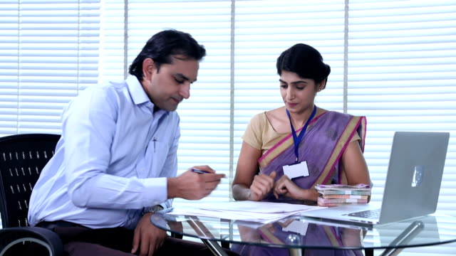 Bank teller giving indian banknote to customer, Delhi, India
