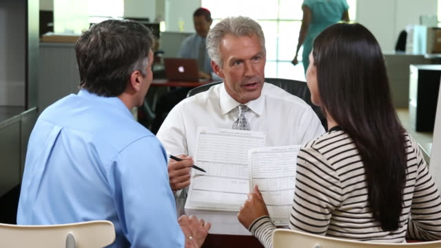 MS PAN Banker Discussing Mortgage Application with Adult Couple in Bank / Richmond, Virginia, USA