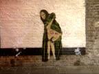 Banksy 'graffiti artworks' ENGLAND London EXT Various shots of Banksy graffiti artworks on walls policeman and dog Mona Lisa showing her bottom dog...