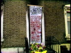 Banner covering doorway of gutted house lists names of thirteen youths who died in fire zoom into yellow wreath with number 13 and flowers resting on...