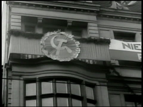 Banner of Polish Coat of Arms White Eagle on building LA Hammer sickle icon on building VS Polish soldiers marching w/ shovels VS German prisoners of...