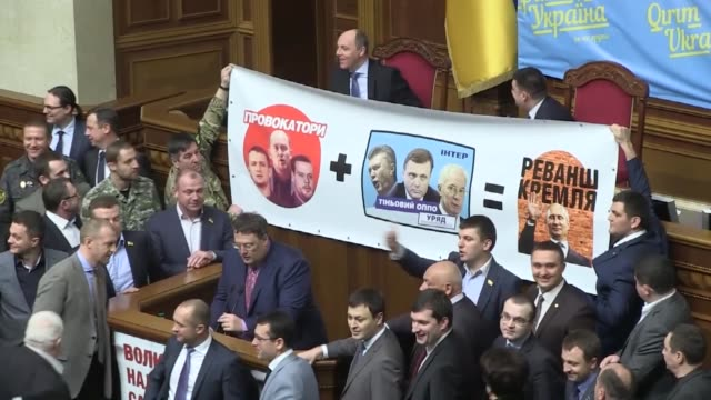A banner on which there are the pictures of Vladimir Putin and some other representatives is hanged over the rostrum at the Ukrainian Parliament in...