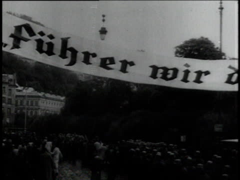 banner stretching across the road above advancing Wehrmacht units reading Fuhrer We Thank You / advancing German Army convoy with cheering civilians...